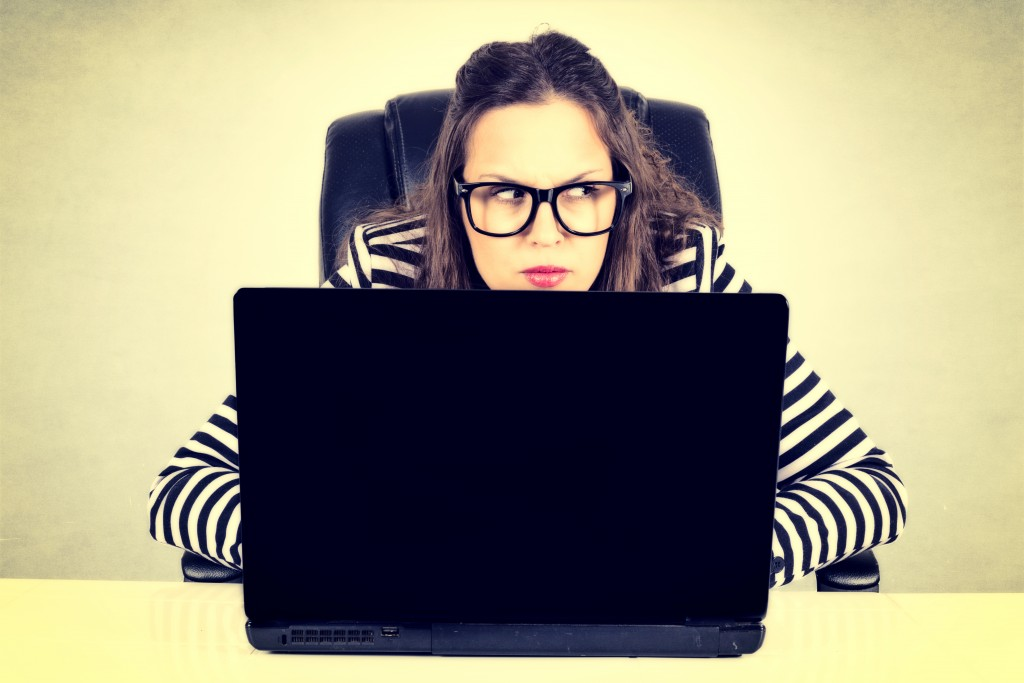 Suspicious businesswoman siting on the desk with laptop computer