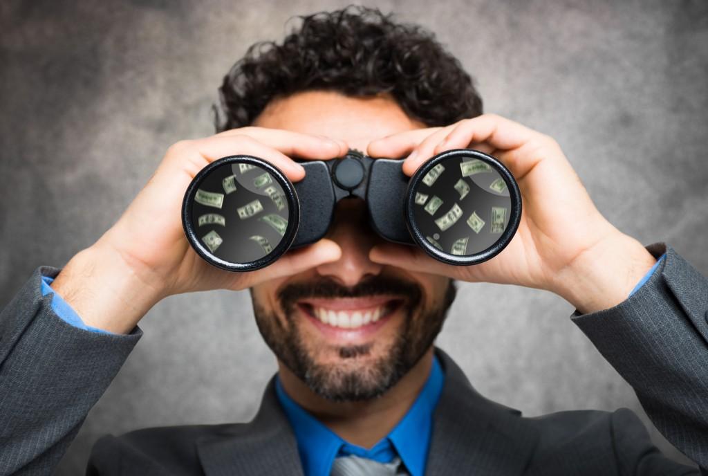 Businessman using binoculars, money reflected in the lens