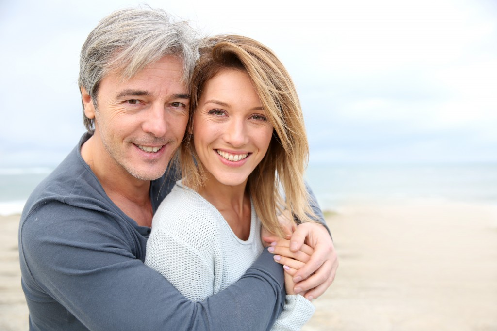 Cheerful mature couple embracing by the beach