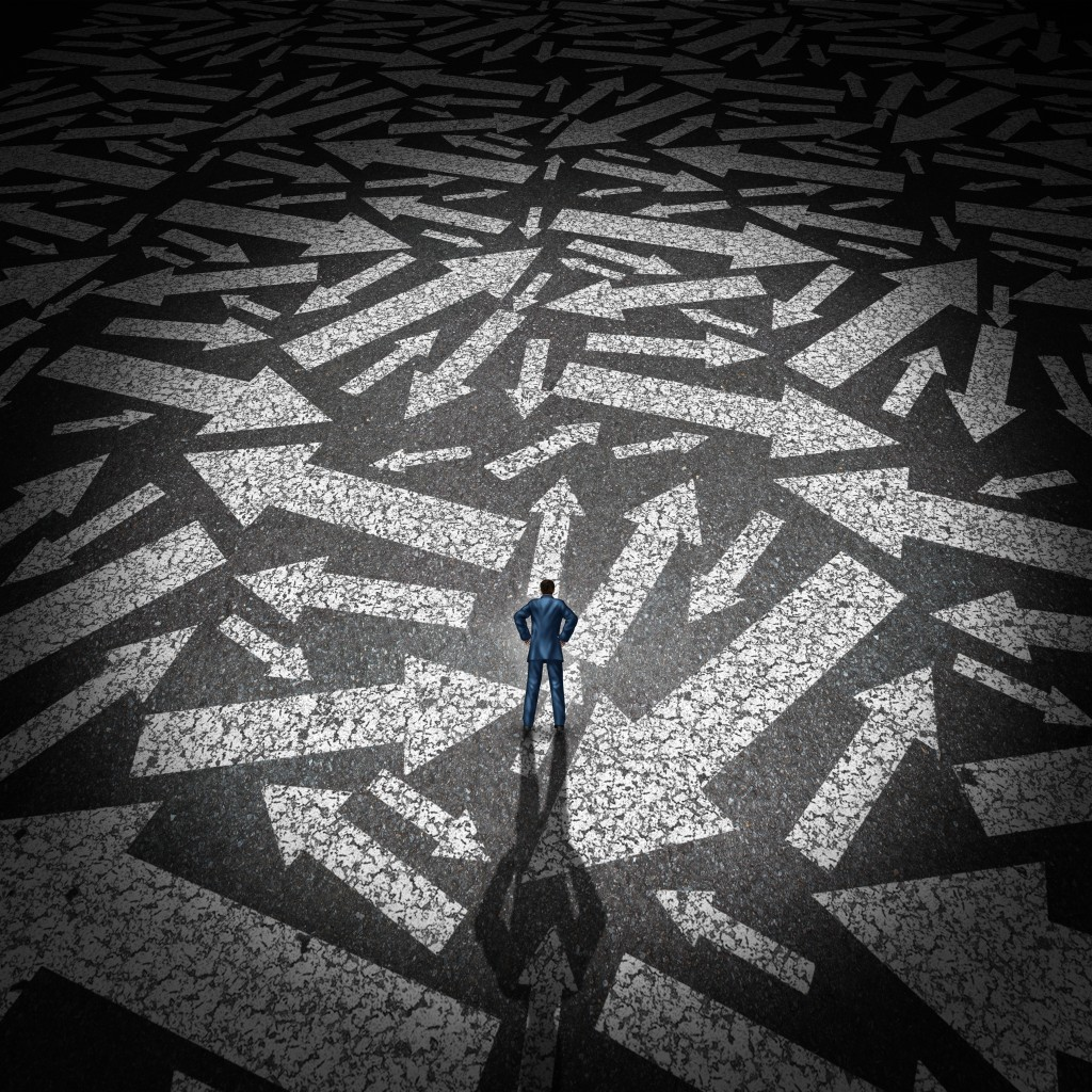 Confused businessman concept as a man standing on a road making a decision on a path to take with a group of arrows going in many directions.