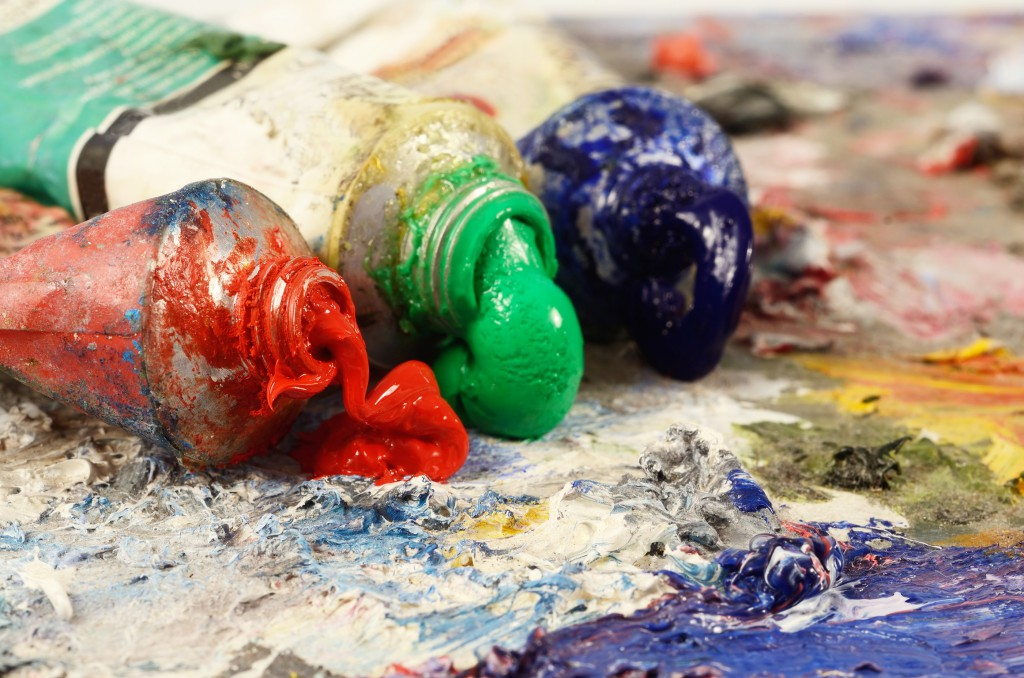 Art still life - closeup of three oil paint tubes with redgreen and blue colours background for creative art design
