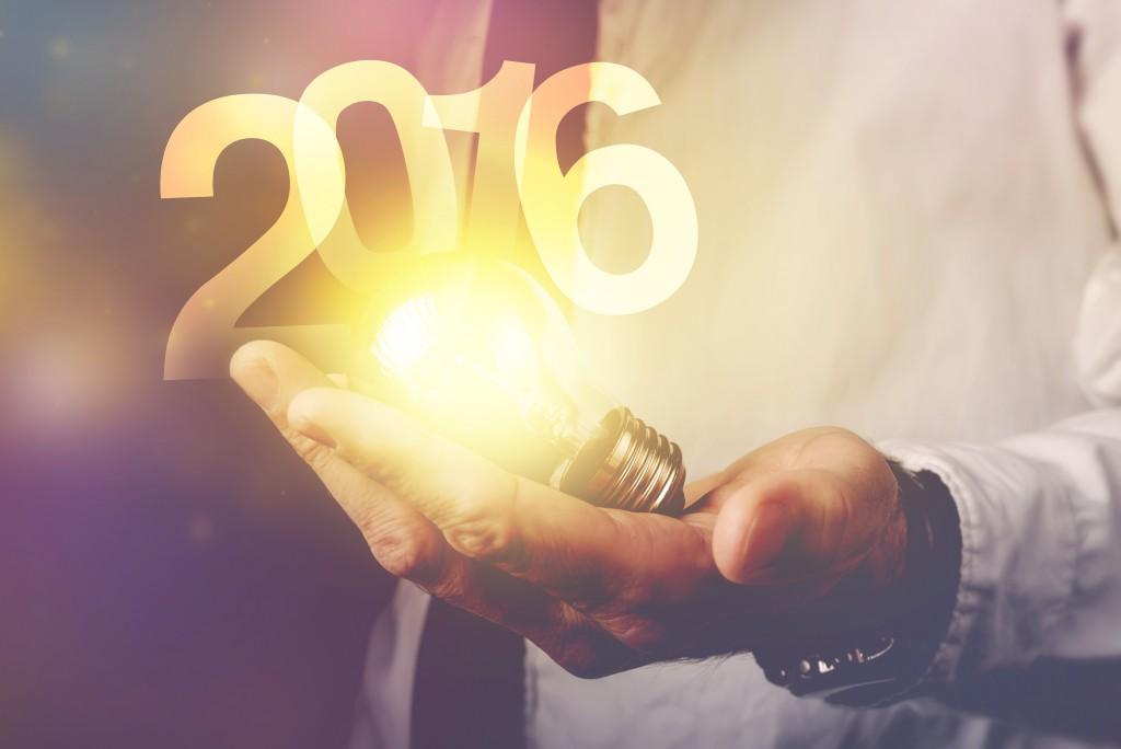 Happy new 2016 business year businessman with light bulb and number 2016 retro toned image selective focus.