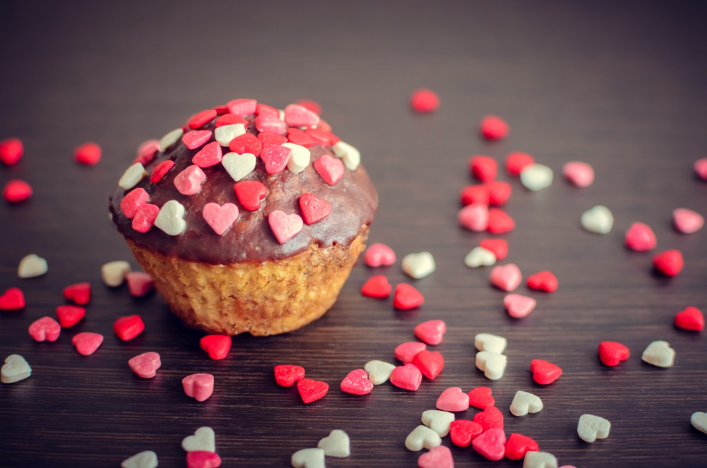 Cupcakes with small hearts on dark wooden background. Romantic love background. Happy Valentines Day. St. Valentine's Day theme.