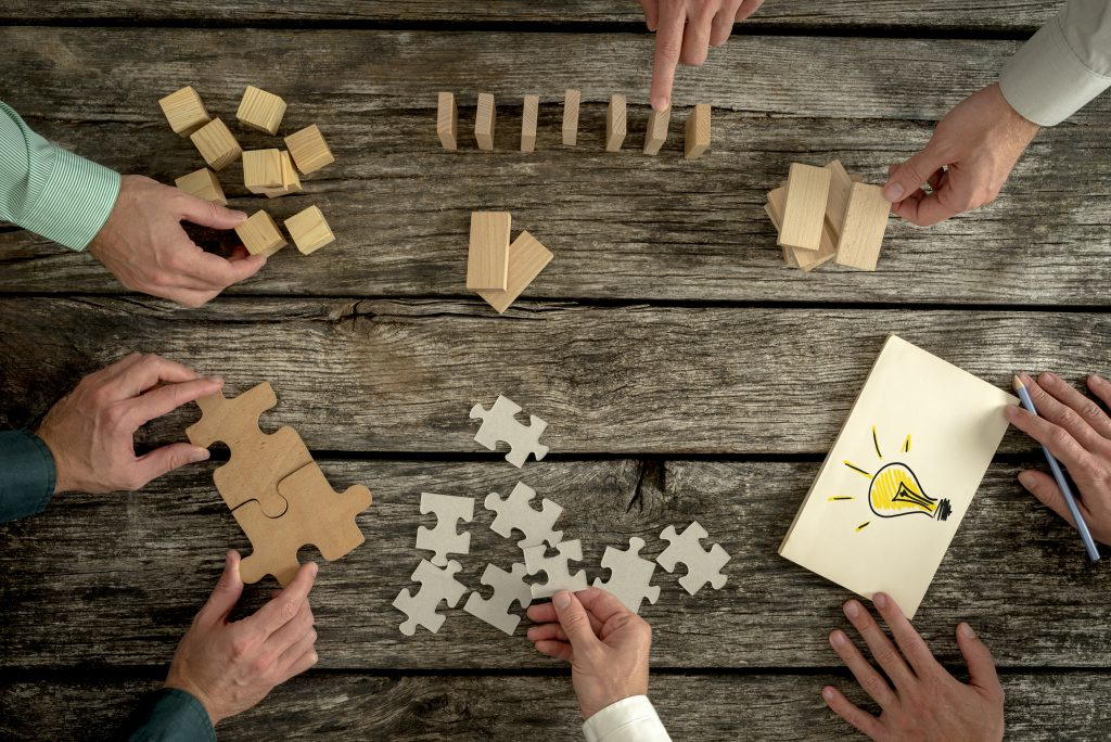 Businessmen planning business strategy while holding puzzle pieces creating ideas with light bulb drawn on paper and rearranging wooden blocks. Conceptual of teamwork strategy vision or education.